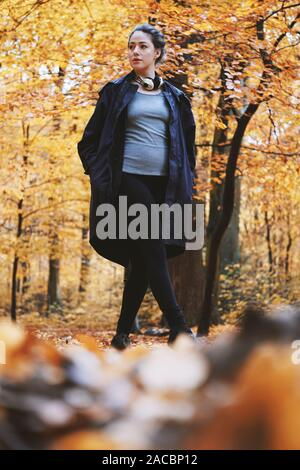 young woman enjoying autumn walk in the woods - candid outdoor lifestyle in fall season - low angle full length view - Stock Photo
