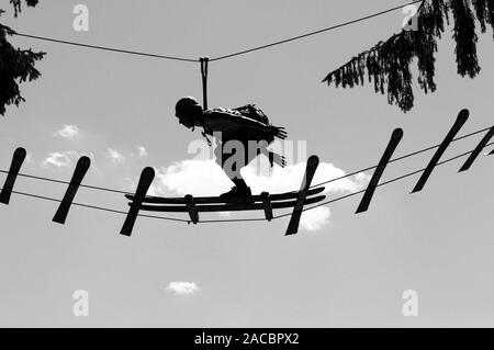 A men is balancing on the skis in the adventure-park in Zillertal valley in Tirol - Stock Photo