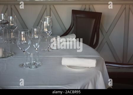 dining table set up and set up with a lot of elegance in the dining room of a restaurant or the dining room of a very rich house, in light white color - Stock Photo