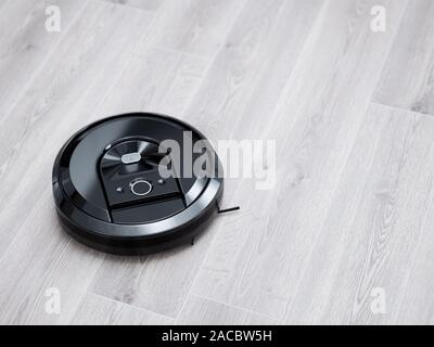 Robotic vacuum cleaner on wood tile floor. 3d rendering illustration. Smart cleaning modern technology - Stock Photo