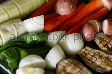 Fresh vegetables prepared with olive oil and spices in a baking tray. Eggplants, onions, potatoes, zucchini, carrots and green peppers. - Stock Photo
