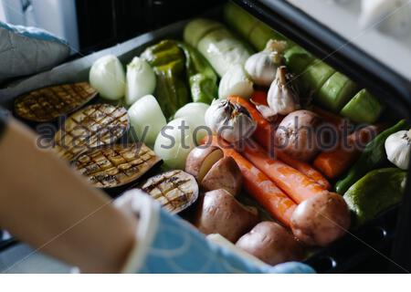 Woman chef taking out a tray of fresh baked vegetables from the oven with blue oven mittens in the kitchen - Stock Photo