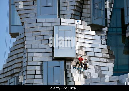 Two workers hanging / abseiling / rappelling while cleaning panels on  Frank Gehry LUMA Foundation building, Luma Arles Cultural Centre, Arles, France - Stock Photo