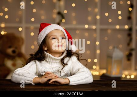 Happy smiling little child girl in santa hat dreaming about the holidays on background with lights. Merry Christmas. copy space - Stock Photo