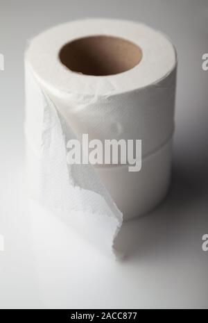 A single roll of white toilet paper. - Stock Photo