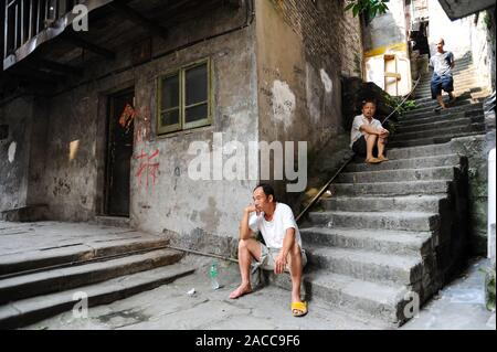 04.08.2012, Chongqing, China, Asia - Men are sitting on a staircase in front of an old house in the old city Shibati. - Stock Photo
