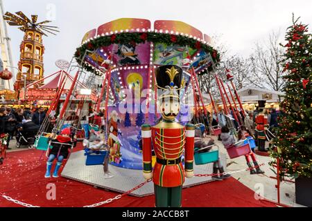 PARIS, FRANCE - NOVEMBER 30, 2019: kids having fun on a swing ride carousel in the Christmas Market at The Tuileries Garden in Paris. A giant wooden p - Stock Photo