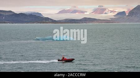 A small boat passing an iceberg in the Kongsfjorden (King's Bay), opposite the Kongsbreen glacier, Spitsbergen. - Stock Photo