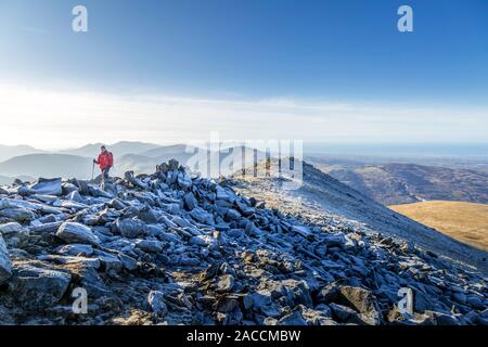 A lone female hiker or walker in winter, walking across the rocky ridge on the top of Elidir Fawr, a mountain in the Snowdonia National Park, Wales. - Stock Photo