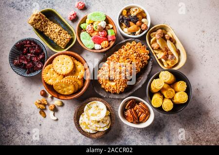 Variety of snacks and sweets on a gray background. Waffles, nuts, sweets, cookies, chips and fruits, top view. - Stock Photo