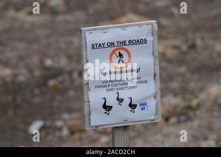 A sign at Ny Alesund warning visitors to stay on the roads to avoid damaging the surrounding landscape. - Stock Photo