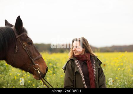 young horsewoman with a horse outeside walking - Stock Photo