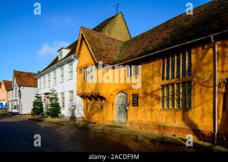 The orange painted Little Hall, which is a late 14th Century timber-famed house in the Market Place, Lavenham, Suffolk, England, UK - Stock Photo