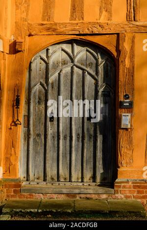 The front doorway of the orange painted exterior of the Little Hall, which is a late 14th Century timber-famed house in the Market Place, Lavenham, Su - Stock Photo