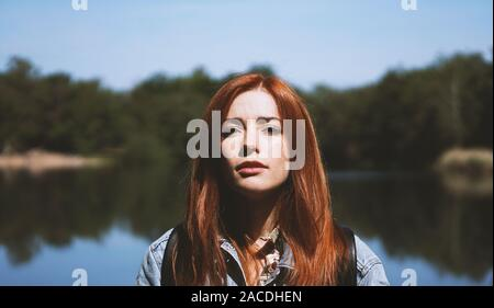 outdoorsy young woman standing by lake in harsh light with deep shadows - authentic real people concept - Stock Photo