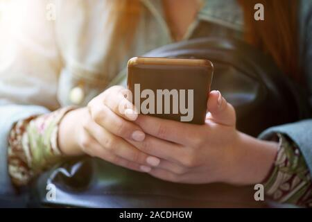 midsection of unrecognizable young woman using her smartphone or mobile phone - trendy filter with sun flare light leak - Stock Photo