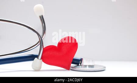 Health care concept: a red fabric heart inside a stethoscope on white table - Stock Photo
