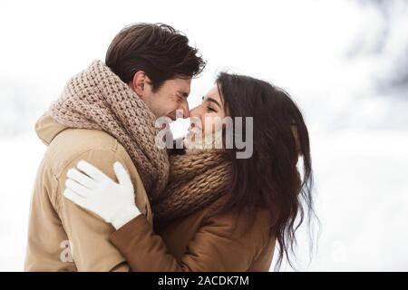 Sweet Couple Rubbing Their Noses Hugging Standing In Snowy Forest