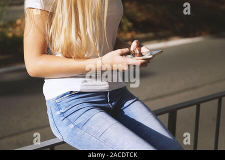 midsection of unrecognizable young woman using her smartphone or mobile phone outside on city street - Stock Photo