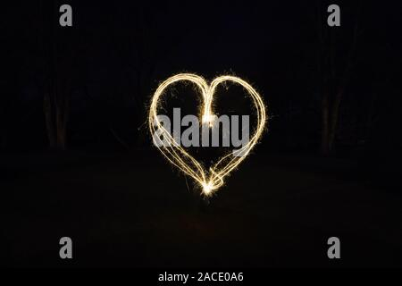 heart shape light painting with sparklers outdoors at night - symbol for love and romance