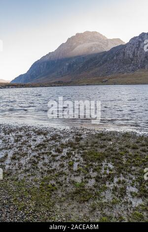 Morning light on snow capped peak of Tryfan from banks of Lake or Llyn Idwal. Snowdonia national Park, Gwynedd, Wales, UK. portrait. - Stock Photo