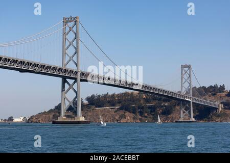 The Western span,Emperor Norton, of the Oakland Bay Bridge in San Francisco Bay with yachts sailing under it. California, United States of America - Stock Photo