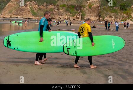 Three people with long boards after surfing walking up the beach at Saunton Sands, North Devon, England, UK - Stock Photo