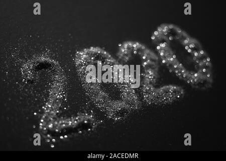2020 shiny silver sparkles pattern on black table. - Stock Photo
