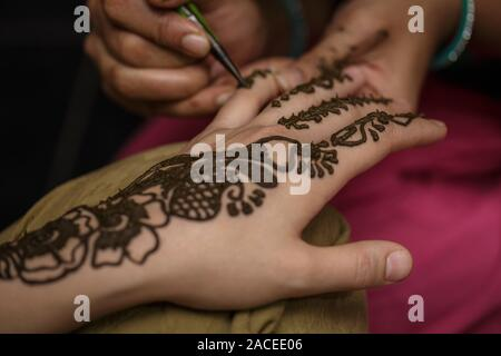 The process of drawing a henna mehendi drawing on the girl hand. Tattoo painting henna - Stock Photo