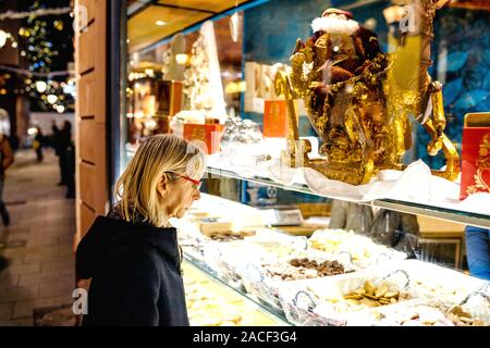 Strasbourg, France - Nov 23, 2017: Side view of senior woman admiring diverse sweets chocolates and cakes in Christian bakery store in central Strasbourg - Stock Photo