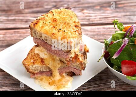 Sandwich with Parmesan and Gruyere cheese, ham, béchamel sauce and artisan bread accompanied by a salad on a wooden background.  The Croque Monsieur. - Stock Photo