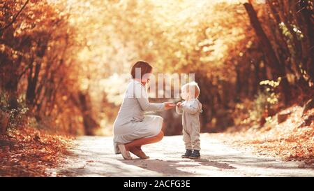 Young mother plays with her son in the autumn forest. Blond in a sports gray suit. Autumn leaves. Joyful family in nature - Stock Photo