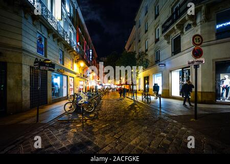 Tourists enjoy a late night walk on a colorful, lively street illuminated by cafe and shop lights in the Latin Quarter district of Paris France. - Stock Photo
