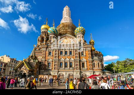 Tourists mingle in the square in front of the medieval onion domes and facade of the Church of the Savior on Spilled Blood in St. Petersburg, Russia. - Stock Photo