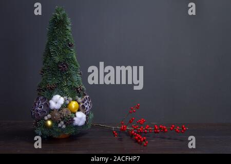Christmas tree made of fir branches and decorated by natural materials and branch with red holly berries - Stock Photo