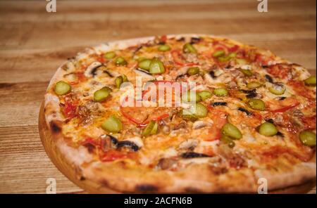 Italian pizza. Delicious fresh pizza served on wooden table - Stock Photo