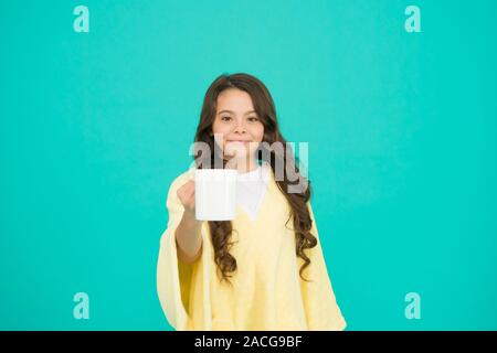 milk for breakfast. happy girl with hot dring in cup. good morning. small kid turquoise wall. little girl drink cocoa or milk before sleeping. cosy and fluffy pajama. feeling comfortable at home. - Stock Photo