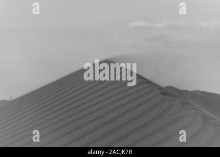 Black and white Sunset in the desert across a textured and patterned ridge with blowing sand making spectacular changing shapes. United Arab Emirates. - Stock Photo