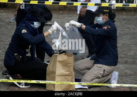 Jakarta, Indonesia. 3rd Dec, 2019. Indonesian police officers collect some evidences at the smoke grenade explosion site in Jakarta, Indonesia, Dec. 3, 2019. An explosion resulted from a smoke grenade took place in Indonesia's National Monument Park (Monas) near the presidential palace in central Jakarta on Tuesday, injuring two soldiers, Jakarta Police Chief Inspector General Gatot Eddy Pramono said. Credit: Aditya Irawan/Xinhua/Alamy Live News - Stock Photo