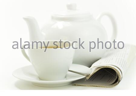 morning cup of tea and press on white - Stock Photo