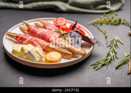 Traditional Italian food is grissini bread with prosciutto, cheese and tomatoes with herbs on a plate on a dark background. Close up