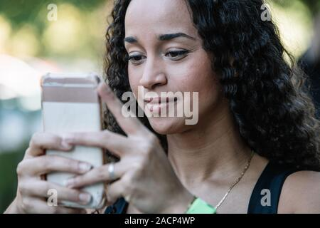 Stock photo of a Detail of the face of a smiling girl looking at the mobile phone - Stock Photo