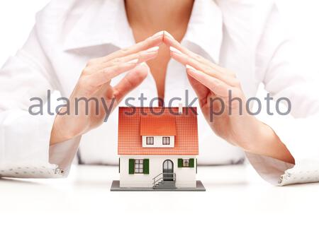 Female hands saving small house with a roof - Stock Photo