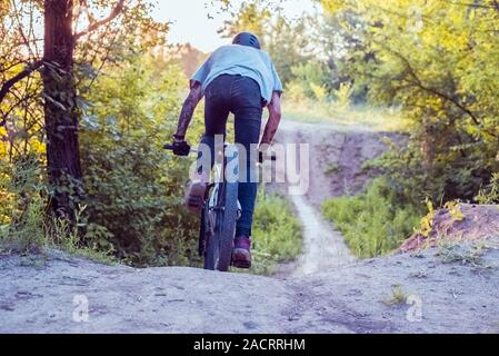 athlete, cyclist rides on a road in the forest. Cycling