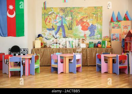 empty tables . refectory of a school for children with chairs and tables without people . School kindergarden nursery dining room . children's - Stock Photo