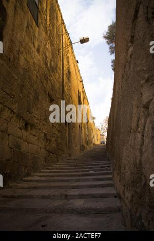 typical narrow street with stairs in the city Valetta on the island of Malta - Stock Photo