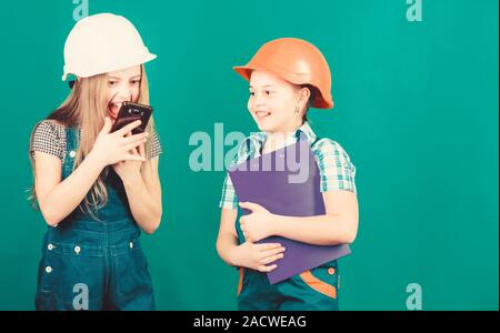 Labor day. 1 may. school project. Foreman inspector. Repair. Little kids in helmet with tablet. small girls repairing together in workshop. shouting on worker in phone call. discussing problems. - Stock Photo