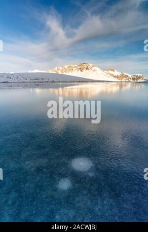 Piz Umbrail reflected in the frozen lake, Braulio Valley, Stelvio Pass, Bormio, Sondrio province, Valtellina, Lombardy, Italy - Stock Photo