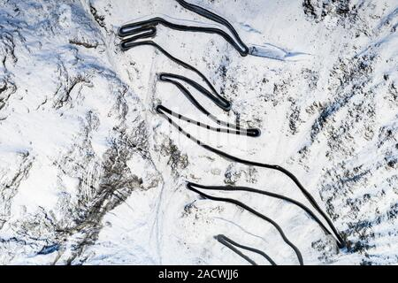 Zig zag shape and steep curves of the snowy Stelvio Pass road from above, Bolzano province, South Tyrol side, Italy