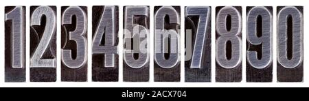 row of ten arabic numerals 0 to 9 in old grunge metal letterpress printing blocks isolated on white - Stock Photo